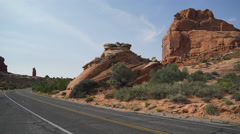 Hitchhiker Walks Along Road in Arches National Park - stock footage