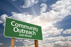 Community Outreach Green Road Sign With Dramatic Clouds and Sky. Stock Photos