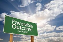 Favorable Outcome Green Road Sign With Dramatic Clouds and Sky. - stock photo