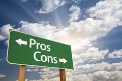 Pros and Cons Green Road Sign With Dramatic Clouds and Sky. - stock photo