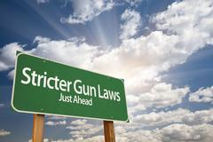 Stricter Gun Laws Green Road Sign With Dramatic Clouds and Sky. - stock photo