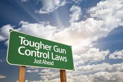 Tougher Gun Control Laws Green Road Sign With Dramatic Clouds and Sky. Stock Photos