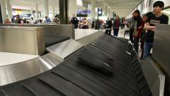 Black soft bag slide down to luggage transporter from luggage outlet conveyor - stock footage