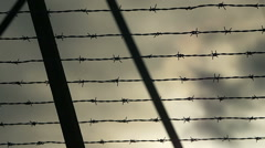 Outside of a prison camp barb wire fence Stock Footage