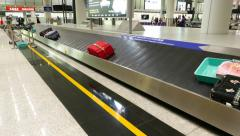 Big red suitcase move on conveyor, baggage carousel, track shot Stock Footage