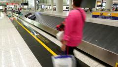 Stock Video Footage of Passenger walk along luggage claim conveyor, suitcases move towards