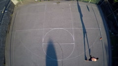 A bird's eye aerial over a basketball player taking a jump shot on an outdoor - stock footage