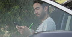 Man using smartphone while waiting for roadside assistance - stock footage