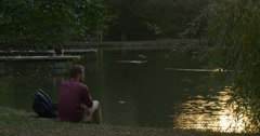 Man is Sitting at The River Lake Bank Backpack is Close Man Throws the Food Stock Footage