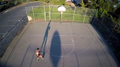 A bird's eye aerial over a basketball player shooting a layup on an outdoor - stock footage