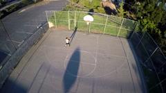 A bird's eye aerial over a basketball player shooting a jump shot on an outdoor - stock footage