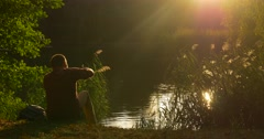 Man is Sitting at The Lake Bank Cover His Face with Hand Throws a Fist Three Stock Footage