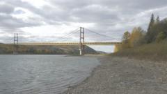 4K Suspension Bridge Panning Shot River Hills Forest Shore Sky Clouds Stock Footage