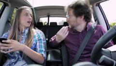 Driving father trying to be nice with his daughter who is playing with phone. Stock Footage