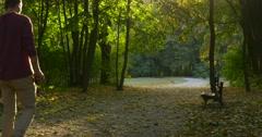 Man is Walking by Park Alley Kicks The Fallen Leaves Flying Dust Walking Slowly Stock Footage