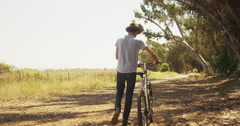 Hispanic man walking down trail with bike Stock Footage