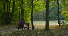 Man is Sitting With His Legs Pursed and Put to the Bench Man Has Stood Up and Stock Footage
