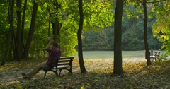 Man is Sitting at The Bench With Bouquet Made Up from Yellow Leaves Man Has Stock Footage
