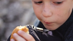 An orphan boy close-up eating bread and holding cap Stock Footage