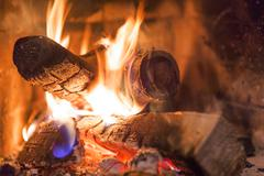 Firewood burning in fireplace fire flame heat red ashes - stock photo