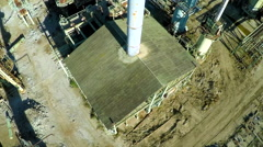Aerial looking down a smokestack over an abandoned oil refinery. - stock footage