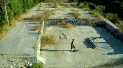 Aerial shot of teenage boys skateboarding in the graffiti covered foundation of - stock footage