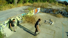 Aerial shot of teenage boys skateboarding in the graffiti covered foundation of Stock Footage