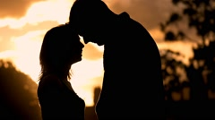 Silhouette of romantic young couple in love park   sunset slow motion lifestyle Stock Footage