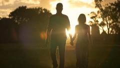 Young couple in love holding hands walking sunset heterosexual lifestyle - stock footage