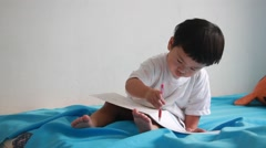 Little boy writing a book on the bed Stock Footage