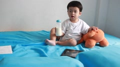 Asian boy drinking milk from bottle on the bed and see tablet. - stock footage