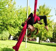 cheerful child training on aerial silks - stock photo