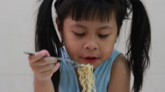 Little girl eating a noodle Stock Footage