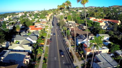 Stock Video Footage of Rising aerial shot over a palm tree lined street in Southern California.