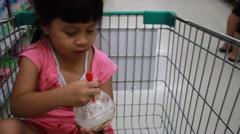Sweet girl eating ice cream and smiling in wheelbarrow Stock Footage