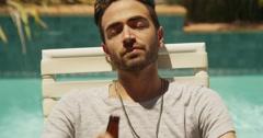 Happy hispanic man sunbathing by the pool - stock footage
