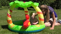 Mother care baby daughter first time in small child pool with water. 4K Stock Footage
