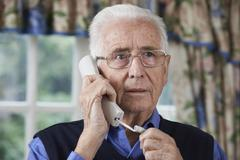 Worried Senior Man Answering Telephone At Home Stock Photos