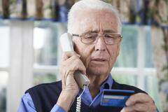 Senior Man Giving Credit Card Details On The Phone Stock Photos