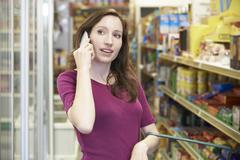 Woman Talking On Mobile Phone In Supermarket Stock Photos
