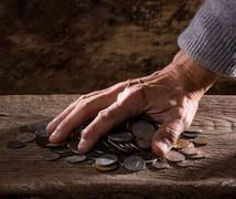 Close up of  caucasian old man's hands  and pile of old coins on a wooden - stock photo