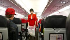 Stewardess in red suit collects rubbish plastic bag, walk close through aisle Stock Footage