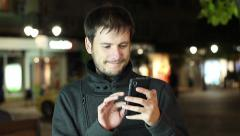 A young bearded man with the phone sends an SMS message in the night city Stock Footage
