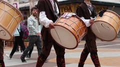 Drummers in traditional costumes of Bulgaria are walking on a busy street - stock footage