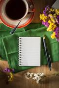 Notepad with pen on wood table - stock photo