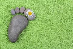 Foot with chamomile on green towel Stock Photos