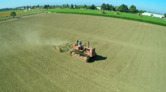 An aerial over a a farm worker driving a tractor across barren fields. - stock footage