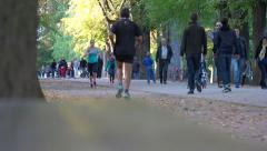Stock Video Footage of Public park, gardens - crowd of family walkers, joggers - sunny late afternoon