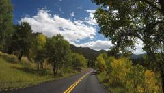 4k POV moving traveling down tree lined mountain road with blue sky clouds - stock footage