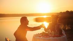 Couple sharing romantic sunset dinner on the beach Stock Footage